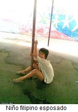 Niño filipino esposado a un poste